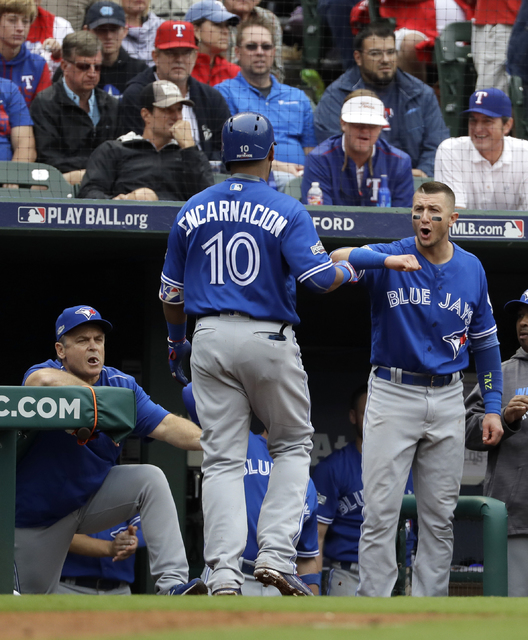 Toronto Blue Jays manager John Gibbons, left, and Troy Tulowitzki, right, celebrate with Edwin Encarnacion (10) after his solo home run off of Texas Rangers' Yu Darvish in the fifth inning of Game ...