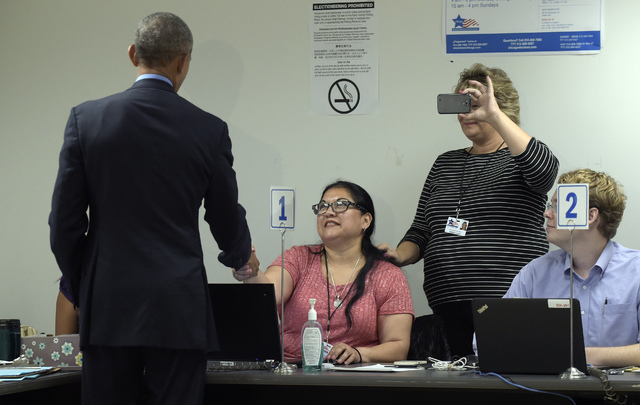 President Barack Obama checks in with poll workers to cast his ballot at the Chicago Board of Elections in the Cook County Office Building in Chicago, Friday, Oct. 7, 2016. Obama is spending the w ...