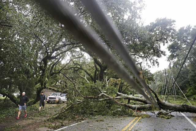 A tree and power lines blown over by Hurricane Matthew lay across a road on St. Simons Island, Ga., Saturday, Oct. 8, 2016. Matthew plowed north along the Atlantic coast, flooding towns and gougin ...