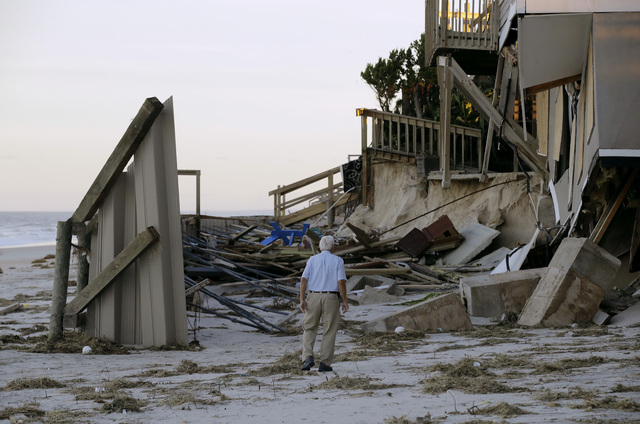 H.V. Bailey looks at damage to a neighbor's home at Ponte Vedra Beach, Fla., Saturday, Oct. 8, 2016, after Hurricane Matthew passed through Friday. (AP Photo/Charlie Riedel)