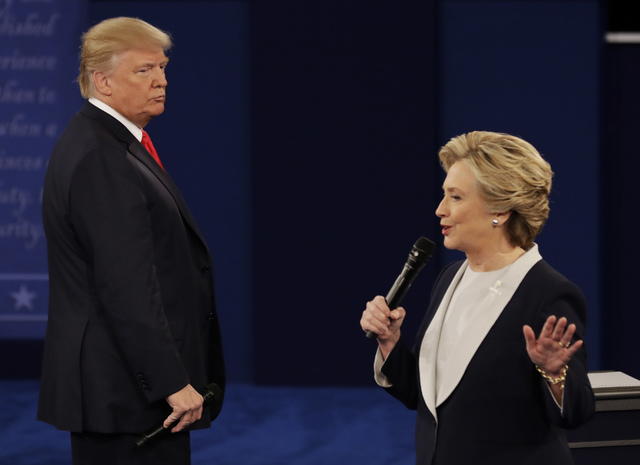 Republican presidential nominee Donald Trump listens to Democratic presidential nominee Hillary Clinton during the second presidential debate at Washington University in St. Louis, Sunday, Oct. 9, ...