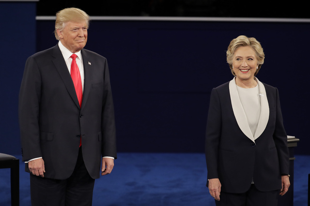 Republican presidential nominee Donald Trump  stands next to Democratic presidential nominee Hillary Clinton during the second presidential debate at Washington University in St. Louis, Sunday, Oc ...