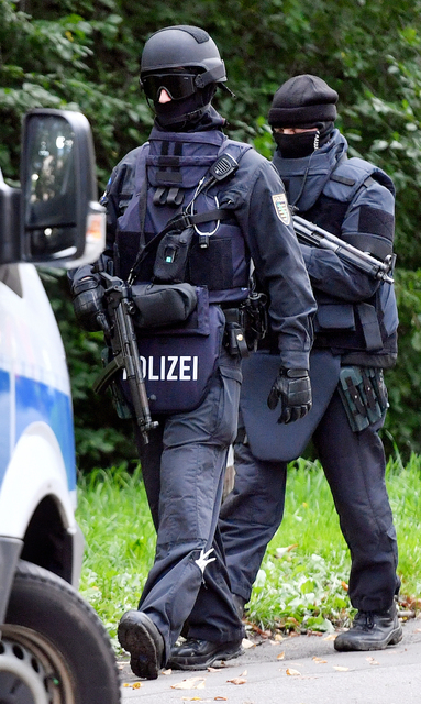 Police walk near an apartment building in the Yorck area of Chemnitz, eastern Germany, Sunday, Oct. 9, 2016. German police searched nationwide for a 22-year-old Syrian man believed to have been pr ...