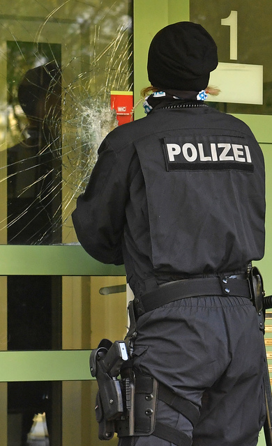 A policewoman closes the damaged door of an apartment building in the Yorck area of Chemnitz, eastern Germany, Sunday, Oct. 9, 2016. German police searched nationwide for a 22-year-old Syrian man  ...