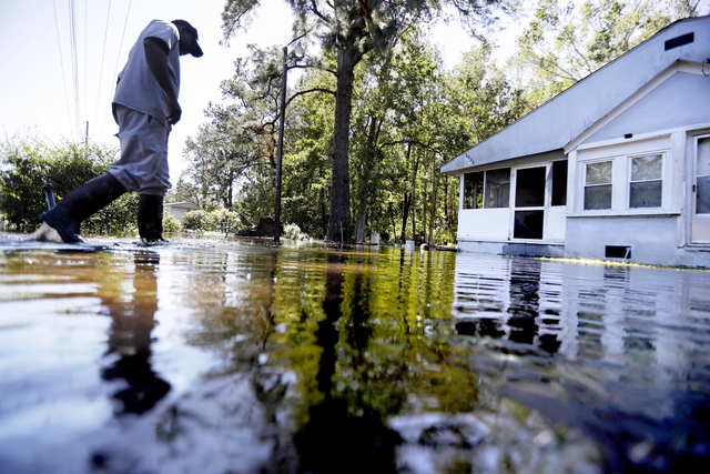 Kyle Simmons wades through water to check on the home of his grandmother following Hurricane Matthew in Edisto Island, South Carolina on Sunday, Oct. 9, 2016. A deteriorating Matthew was stripped  ...