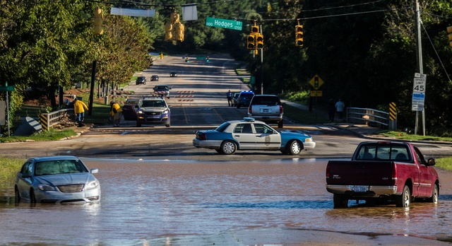 Abandoned cars sit in flood waters on Atlantic Avenue near Crabtree Creek in Raleigh, N.C., after Hurricane Matthew caused downed trees and flooding Sunday, Oct. 9, 2016. (Travis Long/The News &am ...