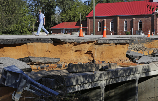 A man walks across a road damaged by floodwaters caused by rain from Hurricane Matthew in Fayetteville, N.C., Sunday, Oct. 9, 2016.  Hurricane Matthew's torrential rains triggered severe flooding  ...
