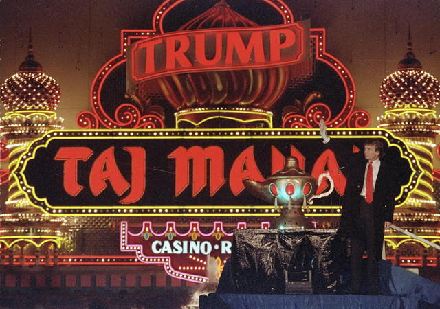 Donald Trump stands next to a genie's lamp as the lights of his Trump Taj Mahal Casino Resort light up during ceremonies to mark its opening in Atlantic City, N.J., April 5, 1990. (Mike Derer/AP)