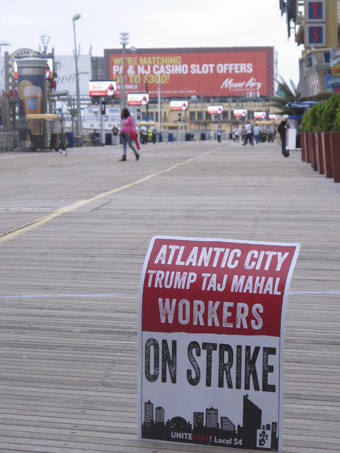 A striker's sign is displayed on the Boardwalk in Atlantic City, N.J., advising of a walkout against the Trump Taj Mahal casino, Oct. 5, 2016. In the background is a billboard advertising a promot ...