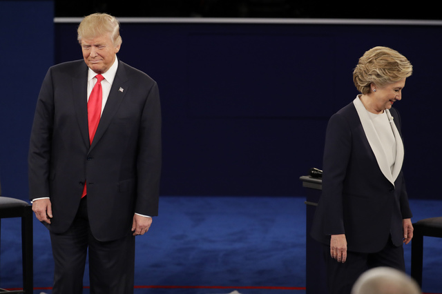 Republican presidential nominee Donald Trump and Democratic presidential nominee Hillary Clinton walk to their positions during the second presidential debate at Washington University in St. Louis ...