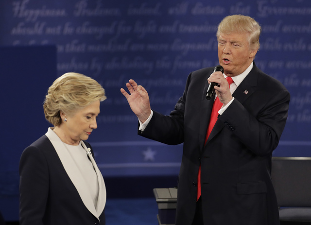 Democratic presidential nominee Hillary Clinton walks past Republican presidential nominee Donald Trump during the second presidential debate at Washington University in St. Louis, Sunday, Oct. 9, ...
