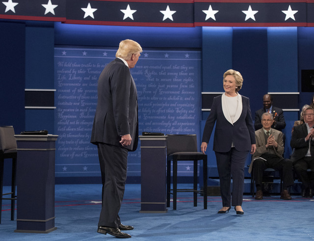 Democratic presidential candidate Hillary Clinton and Republican presidential candidate Donald Trump greet each other at the second presidential debate at Washington University, Sunday, Oct. 9, 20 ...