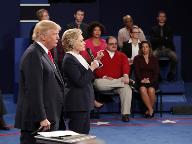 Republican presidential nominee Donald Trump, left, listens as Democratic presidential nominee Hillary Clinton speaks during the second presidential debate at Washington University in St. Louis, S ...