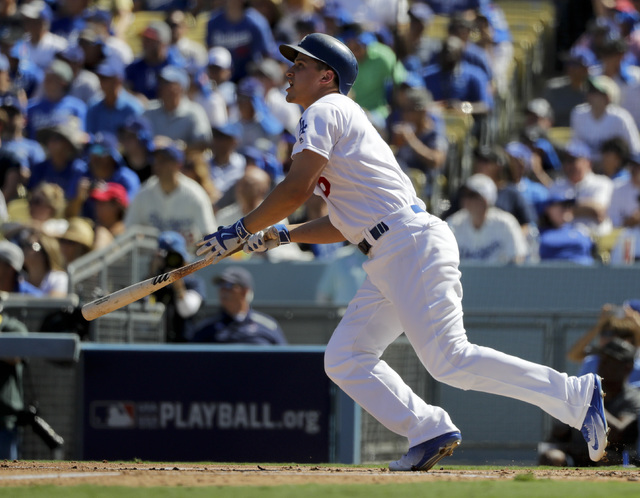 Los Angeles Dodgers' Corey Seager watches his RBI-double during the first inning in Game 3 of baseball's National League Division Series against the Washington Nationals in Los Angeles, Monday, Oc ...
