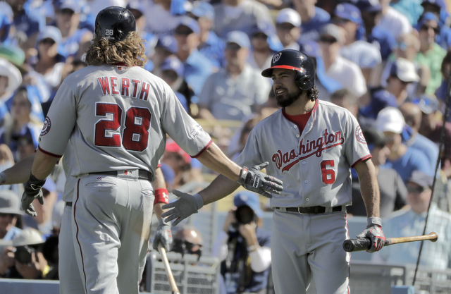 Washington Nationals' Jayson Werth, left, celebrates with Anthony Rendon after scoring  on a single by Bryce Harper during the third inning in Game 3 of baseball's National League Division Series  ...