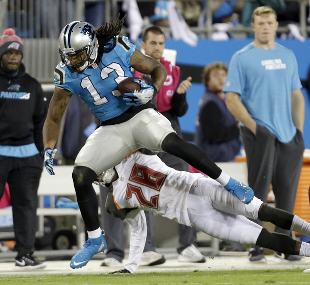 Carolina Panthers' Kelvin Benjamin (13) is knocked out of bounds by Tampa Bay Buccaneers' Vernon Hargreaves (28) in the first half of an NFL football game in Charlotte, N.C., Monday, Oct. 10, 2016 ...