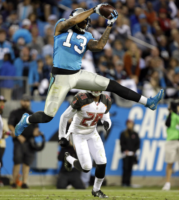 Carolina Panthers' Kelvin Benjamin (13) catches a pass in front of Tampa Bay Buccaneers' Vernon Hargreaves (28) in the first half of an NFL football game in Charlotte, N.C., Monday, Oct. 10, 2016. ...