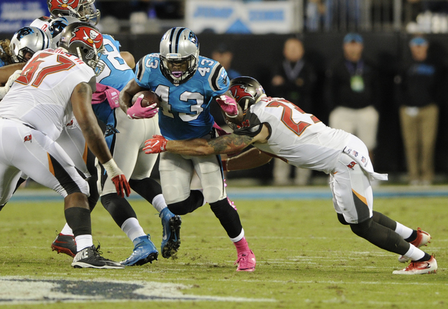 Carolina Panthers' Fozzy Whittaker (43) is tackled by Tampa Bay Buccaneers' Chris Conte (23) in the first half of an NFL football game in Charlotte, N.C., Monday, Oct. 10, 2016. (AP Photo/Mike McCarn)