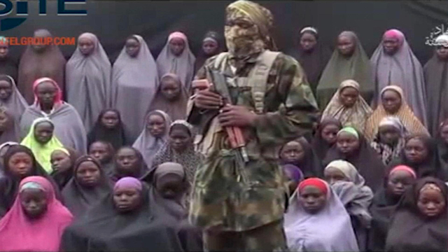 In an image taken from video distributed Aug. 14, 2016, an alleged Boko Haram soldier standing in front of a group of girls believed to be some of the 276 abducted Chibok schoolgirls held since Ap ...