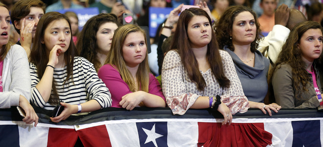 A group of young women listen to first lady Michelle Obama speak during a campaign rally for Democratic presidential candidate Hillary Clinton Thursday, Oct. 13, 2016, in Manchester, N.H. (AP Phot ...