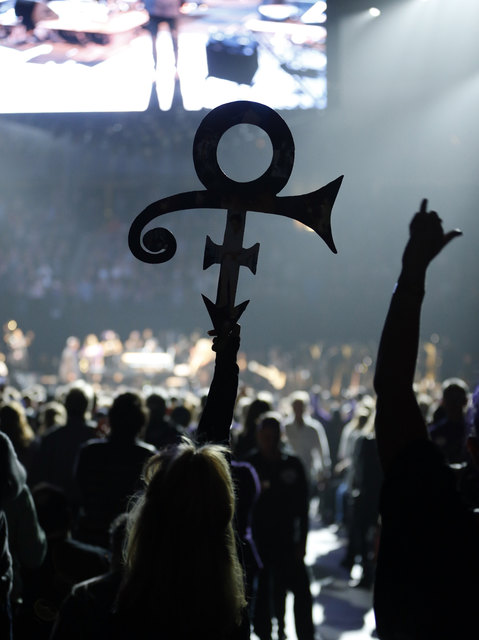 A Prince fan holds up his symbol Thursday, Oct. 13, 2016, in St. Paul, Minn., during a tribute concert honoring the late musician who died in April.  (Jim Mone/AP)