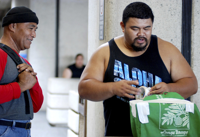 In this Oct. 10, 2016 photo, Mua Migi, left, watches his son Atimua Migi put tape on a carry-on bag before boarding a Hawaiian Airlines flight to Pago Pago, American Samoa at Honolulu Internationa ...