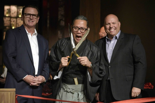 Masaharu Morimoto jokes with ribbon-cutting scissors while flanked by MGM Grand President and COO Scott Sibella and MGM Grand Vice President of Food and Beverage Jason Shkorupa during the grand op ...