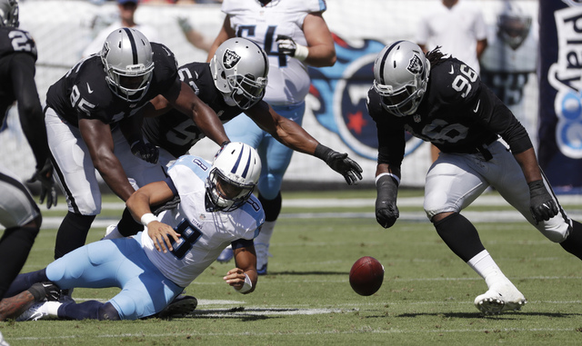 FILE -- In this Sept. 25, 2016 file photo, Tennessee Titans quarterback Marcus Mariota (8) fumbles the ball as Oakland Raiders defenders Jihad Ward (95) and Denico Autry (96) close in during an NF ...