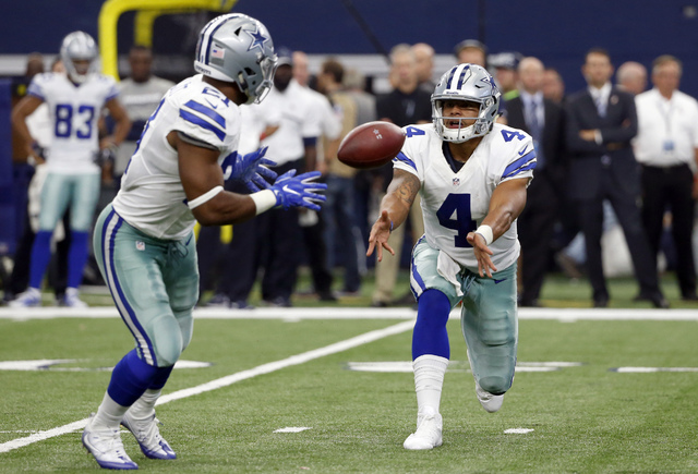 In this Sept. 11, 2016, file photo, Dallas Cowboys quarterback Dak Prescott (4) pitches the ball to running back Ezekiel Elliott (21) during an NFL football game against the  New York Giants in Ar ...
