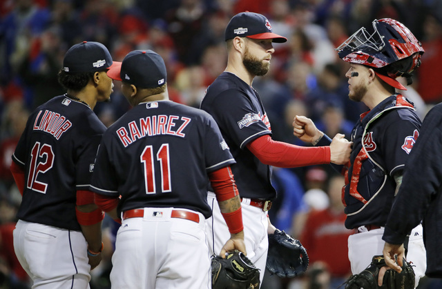 Cleveland Indians starting pitcher Corey Kluber, second from right, and catcher Roberto Perez congratulate one another as Kluber leaves during the seventh inning against the Toronto Blue Jays in G ...