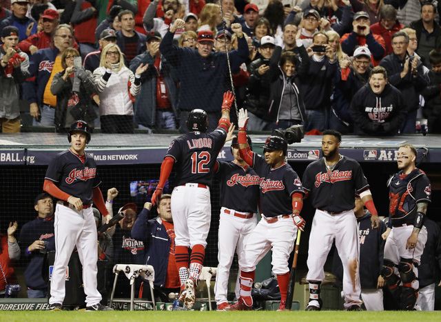 Cleveland Indians' Francisco Lindor (12) celebrates with teammates after his two-run home run against the Toronto Blue Jays during the sixth inning in Game 1 of baseball's American League Champion ...