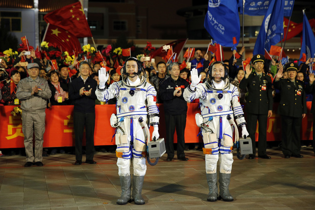 Chinese astronauts Jing Haipeng, right, and Chen Dong, wave farewell before being launched into space. The astronauts will dock with an experimental space station and stay there for 30 days to tes ...