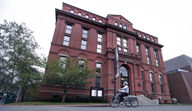 A cyclist earlier this month rolls past the Peabody Museum of Archaeology & Ethnology at Harvard University in Cambridge, Massachusetts. The Peabody, one of the oldest and largest museums in t ...