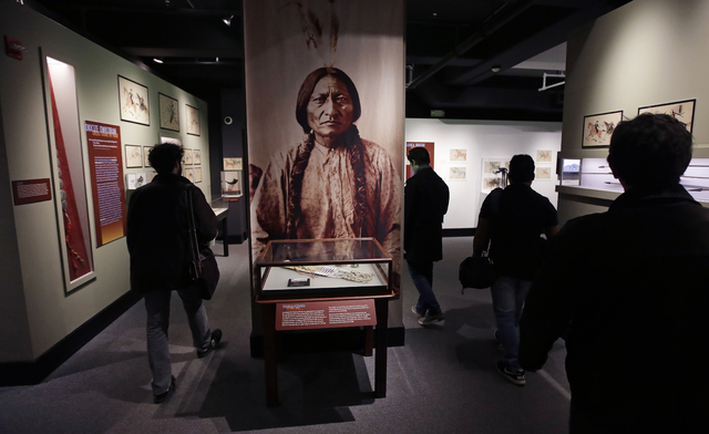 Patrons pass a portrait featuring Sitting Bull, part of the Hall of North American Indian exhibit, at the Peabody Museum of Archaeology & Ethnology at Harvard University in Cambridge, Mass., T ...