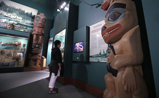 A visitor stands among totem poles as she watches a video as part of Hall of the North American Indian exhibit, at the Peabody Museum of Archaeology & Ethnology at Harvard University. (Charles ...