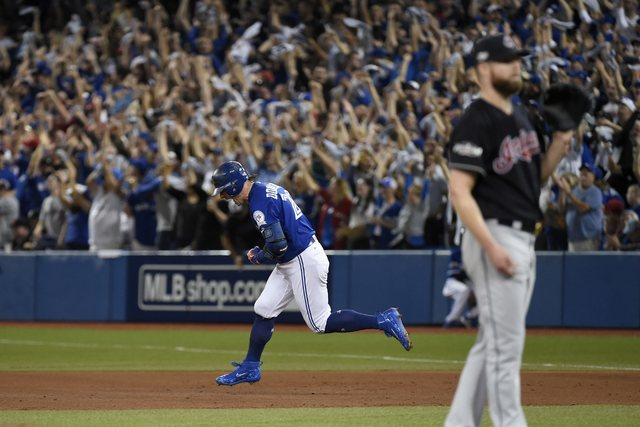 Toronto Blue Jays third baseman Josh Donaldson (20) reacts as he rounds the bases on a solo home run against Cleveland Indians pitcher Corey Kluber (right) during third inning, game four American  ...