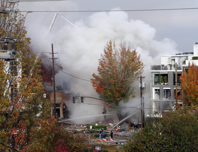 Smoke rises as firefighters battle a blaze after a gas explosion in Portland, Ore., Wednesday, Oct. 19, 2016. A powerful natural gas explosion that neighbors said felt like an earthquake rocked th ...