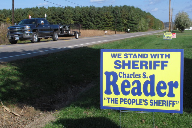A truck passes a sign for the election of Pike County Sheriff Charles Reader in Waverly, Ohio. The still-unsolved killing of eight members of the Rhoden family, an investigation overseen by Reader ...