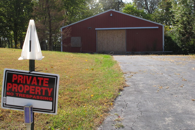 A private property sign guards the boarded up garage on property on Union Hill Road, Tuesday, Oct. 18, 2016, near the trailer where the bodies of Dana Rhoden and her two children were found on Apr ...