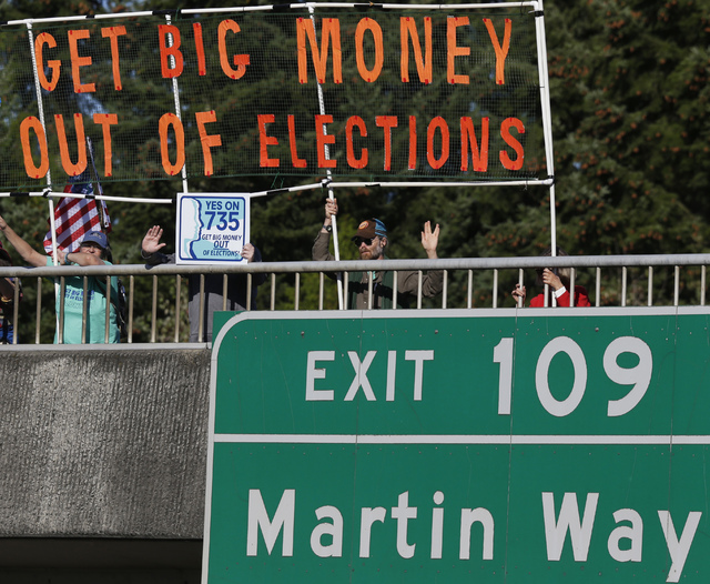 In this Sept. 22, 2016, file photo, supporters of Initiative 735 hold a banner above the I-5 freeway during the evening commute in Lacey, Wash.  Voters are disgusted with the way campaigns are pai ...