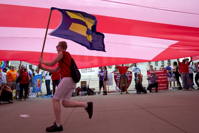 """In this June 26, 2015, file photo, a supporter of same-sex marriage runs with an """"equality"""" flag under a larger """"equality"""" drape outside of the Supreme Court in Washington, before the court declar ..."""