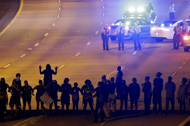 In this Sept. 22, 2016. file photo, protesters block I-277 during a third night of unrest following the police fatal shooting of Keith Lamont Scott in Charlotte, N.C. Policing in the United States ...