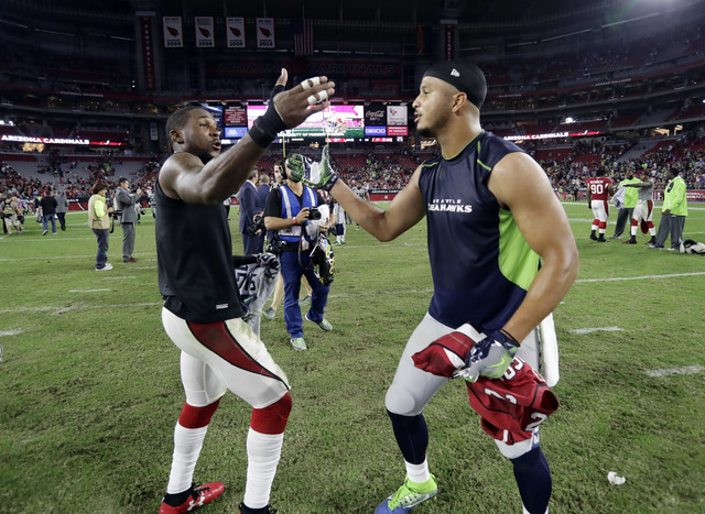 Arizona Cardinals cornerback Patrick Peterson, left, embraces Seattle Seahawks wide receiver Jermaine Kearse after exchanging jerseys after an NFL football game, Sunday, Oct. 23, 2016, in Glendale ...