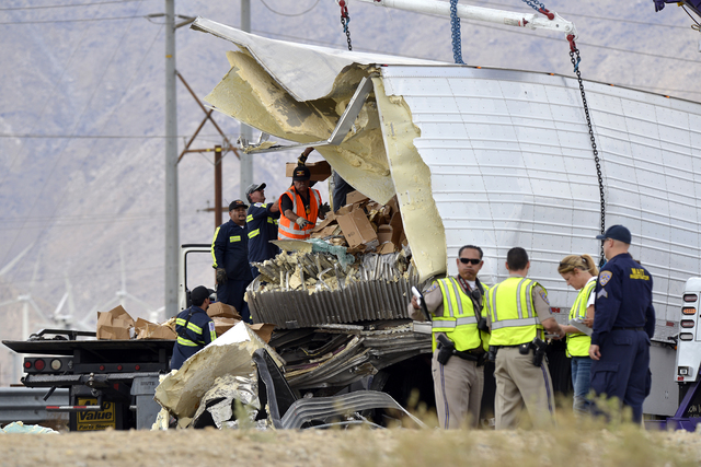 Workers remove debris from a semi-truck that crashed with a tour bus on Interstate 10, west of the Indian Canyon Drive off-ramp, in Desert Hot Springs, near Palm Springs, Calif., Sunday, Oct. 23,  ...