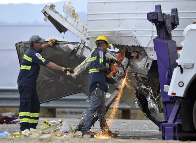 Workers remove wreckage from a semi-truck that crashed with a tour bus on Interstate 10, west of the Indian Canyon Drive off-ramp, in Desert Hot Springs, near Palm Springs, Calif., Sunday, Oct. 23 ...