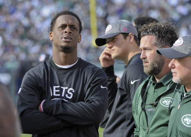 New York Jets quarterback Geno Smith, left, watches play from the sidelines after leaving the game with a knee injury during the third quarter of an NFL football game against the Baltimore Ravens, ...