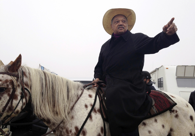 Civil rights activist Jesse Jackson sits atop a horse Wednesday, Oct. 26, 2016, while visiting the protest camp against the Dakota Access oil pipeline outside Cannon Ball, N.D. Jackson said he cam ...