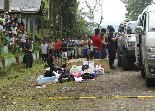 Residents watch as police inspect the contents of the vehicles following a gunbattle on Friday that killed Mayor Samsudin Dimaukom of southern Datu Saudi Ampatuan township and nine others. (AP Photo)