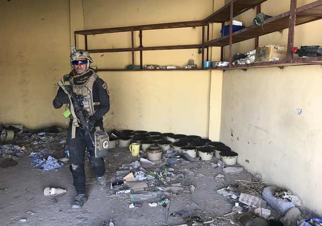 A soldier with Iraq's elite counterterrorism force walks through a building near to a tunnel made by Islamic State militants in Bartella, Iraq, Thursday, Oct. 27, 2016. The town of Bartella in nor ...