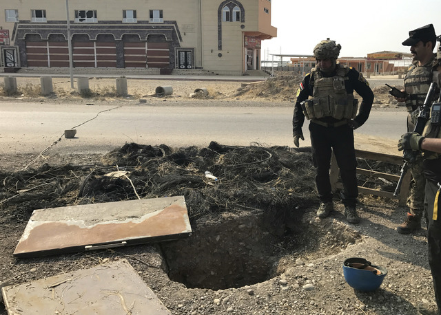 A soldier with Iraq's elite counterterrorism force inspects a tunnel made by Islamic State militants in Bartella, Iraq, Thursday, Oct. 27, 2016. The town of Bartella in northern Iraq lays about 20 ...